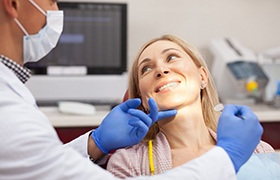 Woman in dental chair during cosmetic consultation.