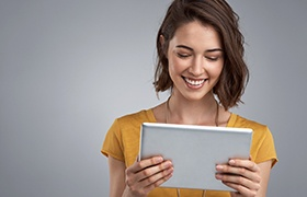 Smiling woman looking at tablet computer