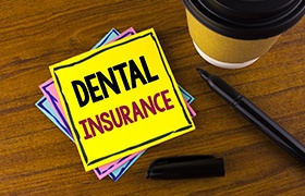 Dental insurance written on yellow post it note
