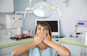 anxious woman sitting in dental chair and covering mouth with hands