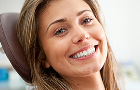 Happy woman smiling in dental chair
