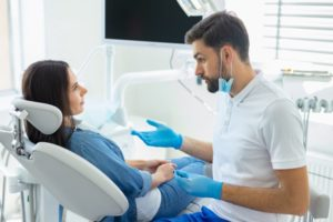 Dentist speaking to woman sitting in dental chair