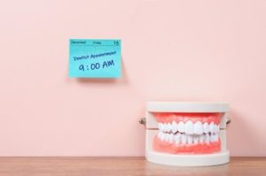 """A sticky note on a wall reading """"dental appointment, 9 am"""" next to a dental diagram"""