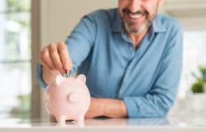 man putting coins into a pink piggy bank that he saved by getting dental implants in Aurora