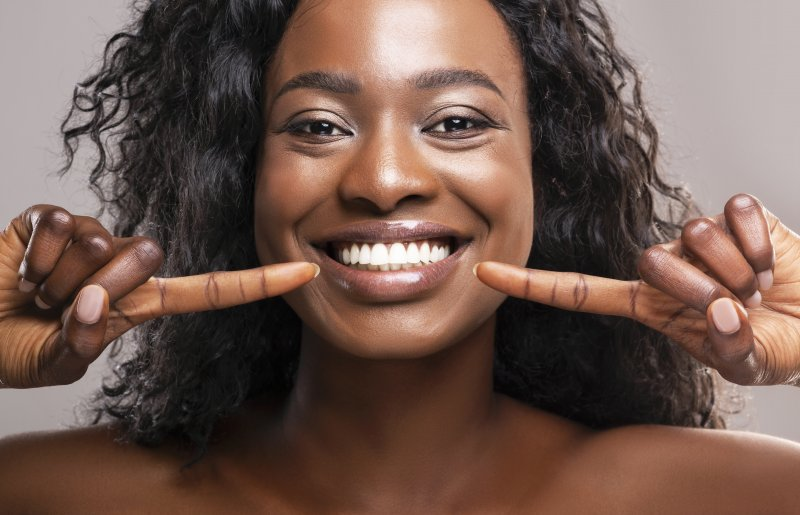 young woman pointing to perfect white smile